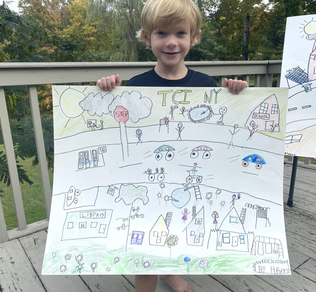 young boy with hand-drawn poster advocating for TCI