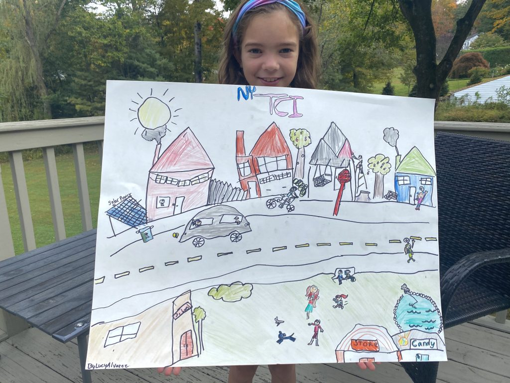 young girl with poster advocating for TCI