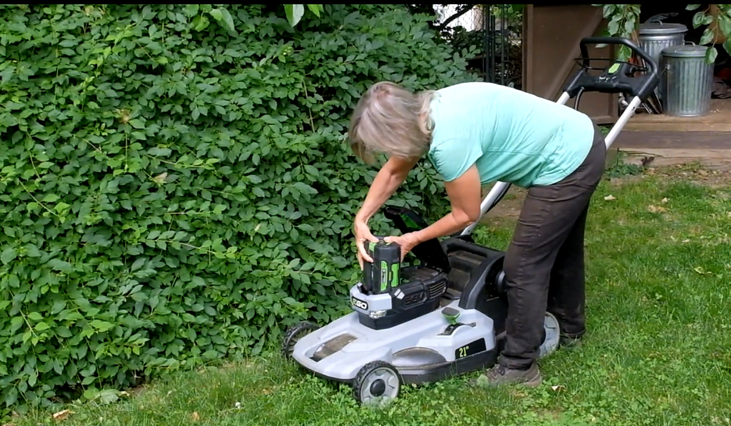 woman putting battery in electric lawn mower