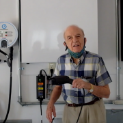 man standing by electric car charger in his garage