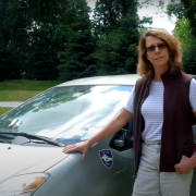 woman standing by hybrid vehicle