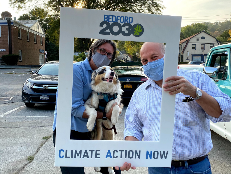"2 men and a very cute dog pose with a photo frame sign that reads ""Climate Action Now"""