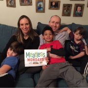 family sitting on couch with Meatless Monday sign