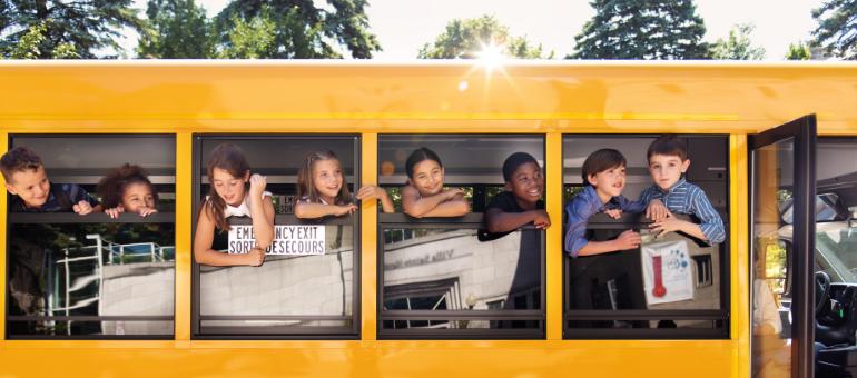kids wave from window of a school bus